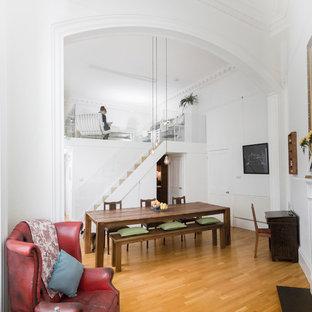 Идея дизайна: маленькая гостиная-столовая в современном стиле с белыми стенами, паркетным полом среднего тона и стандартным камином