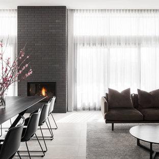 メルボルンのコンテンポラリースタイルのおしゃれなダイニング (白い壁、セラミックタイルの床、標準型暖炉、レンガの暖炉まわり、グレーの床) の写真