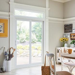 Modelo de comedor de estilo de casa de campo, de tamaño medio, cerrado, con paredes grises, suelo de baldosas de porcelana y suelo beige