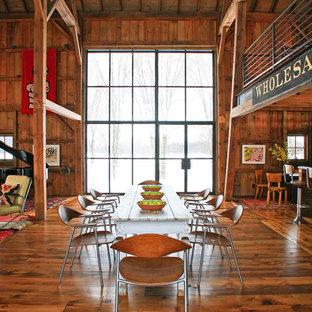 Aménagement d'une salle à manger ouverte sur le salon campagne avec un sol en bois foncé.