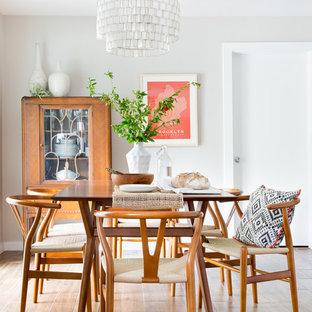 Foto di una sala da pranzo aperta verso la cucina minimalista di medie dimensioni con pareti beige, pavimento in laminato, nessun camino e pavimento marrone