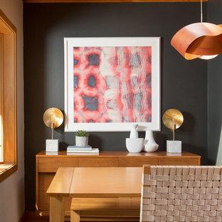 シアトルの小さいミッドセンチュリースタイルのおしゃれなダイニングキッチン (黒い壁、無垢フローリング、両方向型暖炉、レンガの暖炉まわり、黄色い床) の写真