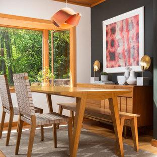 Ejemplo de comedor de cocina vintage, pequeño, con paredes negras, suelo de madera en tonos medios, chimenea de doble cara, marco de chimenea de ladrillo y suelo amarillo