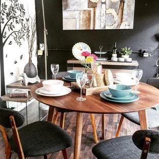 Diseño de comedor retro, pequeño, abierto, con paredes negras y suelo laminado