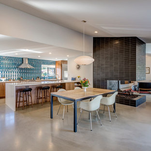 Foto di una sala da pranzo aperta verso la cucina minimalista con pavimento in cemento, cornice del camino piastrellata, pavimento grigio, pareti bianche e camino bifacciale