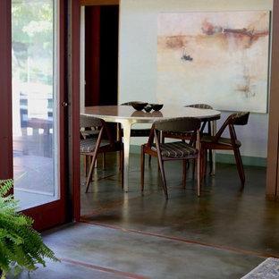 Ispirazione per una sala da pranzo aperta verso la cucina chic di medie dimensioni con pareti verdi, pavimento in cemento, camino classico, cornice del camino in mattoni e pavimento verde