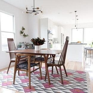 Idée de décoration pour une salle à manger ouverte sur la cuisine tradition avec un sol en bois clair, un mur blanc, aucune cheminée et un sol rose.