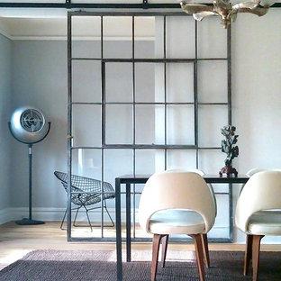 Esempio di una sala da pranzo industriale chiusa e di medie dimensioni con pareti grigie e parquet chiaro