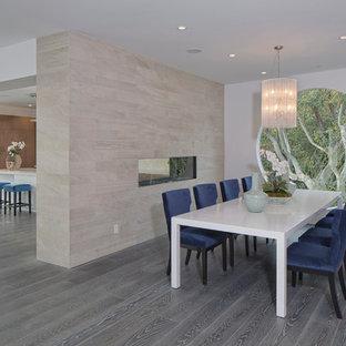 Modelo de comedor retro, grande, abierto, con paredes blancas, suelo vinílico, chimenea de doble cara, marco de chimenea de madera y suelo gris