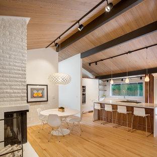 Immagine di una sala da pranzo aperta verso la cucina moderna con pareti bianche, pavimento in legno massello medio, camino bifacciale, cornice del camino in mattoni e pavimento bianco