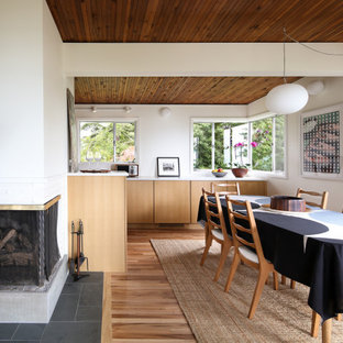 Mid-sized mid-century modern medium tone wood floor and brown floor kitchen/dining room combo photo in Seattle with white walls, a corner fireplace and a brick fireplace