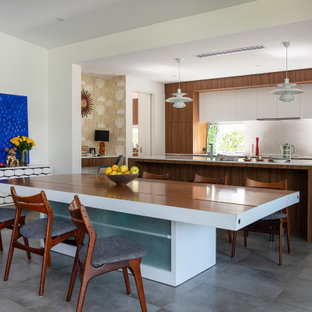 Photo of a midcentury kitchen/dining combo in Perth with white walls, concrete floors, no fireplace, grey floor and wallpaper.