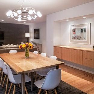 Idée de décoration pour une grand salle à manger ouverte sur le salon avec un mur gris, un sol en bois clair, une cheminée standard, un manteau de cheminée en carrelage et un sol bleu.