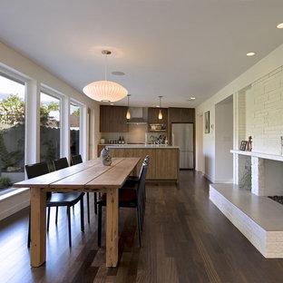 Exempel på en modern matplats med öppen planlösning, med en spiselkrans i tegelsten och vita väggar