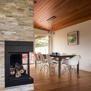 Idee per una sala da pranzo minimalista con pareti bianche, pavimento in legno massello medio, camino ad angolo e cornice del camino in pietra
