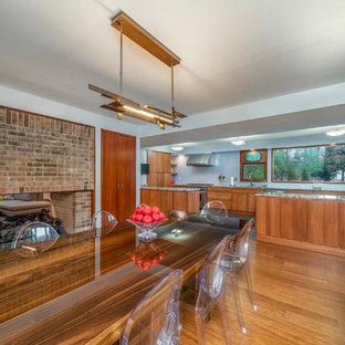 Foto di una sala da pranzo aperta verso la cucina minimalista di medie dimensioni con pareti blu, camino bifacciale, cornice del camino in mattoni e pavimento in sughero