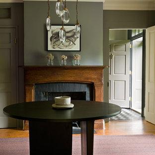 Foto di una piccola sala da pranzo eclettica chiusa con pareti grigie, parquet chiaro, camino classico e cornice del camino in legno