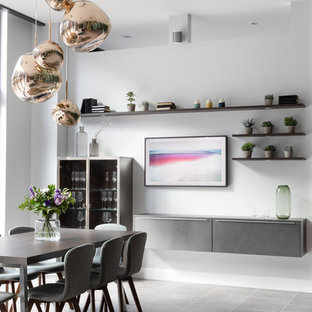 Contemporary dining room in West Midlands with white walls and grey floors.
