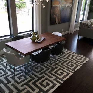 Foto di una piccola sala da pranzo moderna con pareti grigie, parquet scuro, camino classico, cornice del camino in metallo e pavimento marrone