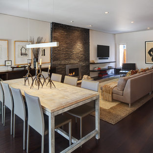 Modern inredning av en mellanstor matplats med öppen planlösning, med mörkt trägolv, vita väggar, en bred öppen spis, en spiselkrans i metall och brunt golv
