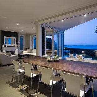 オークランドの大きいビーチスタイルのおしゃれなダイニングキッチン (淡色無垢フローリング、グレーの壁、両方向型暖炉) の写真