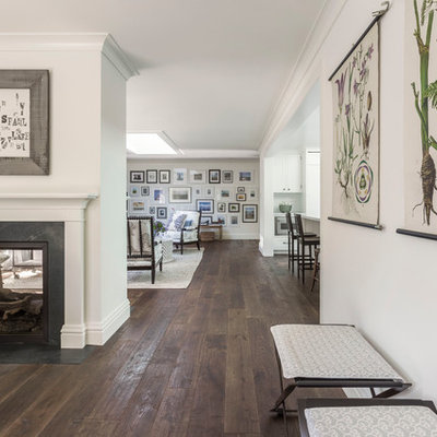 Inspiration for a mid-sized farmhouse dark wood floor great room remodel in San Francisco with white walls, a two-sided fireplace and a stone fireplace
