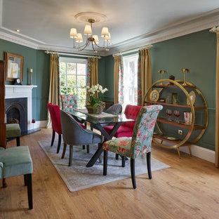 На фото: отдельная столовая среднего размера в классическом стиле с зелеными стенами, паркетным полом среднего тона, угловым камином и коричневым полом