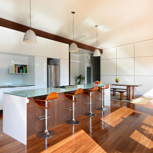Photo of a contemporary eat-in kitchen in Wollongong with glass benchtops, white splashback, stainless steel appliances, bamboo floors, with island, an undermount sink, flat-panel cabinets, white cabinets and glass sheet splashback.