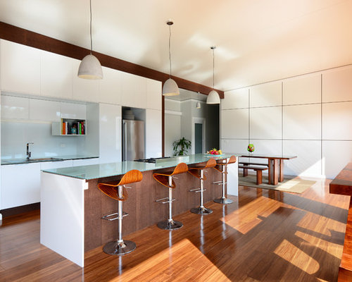 photo of a contemporary eat in kitchen in wollongong with glass benchtops white splashback - Glass Sheet Kitchen Design