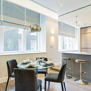 This is an example of a large contemporary open plan dining room in London with beige walls, no fireplace, medium hardwood flooring and beige floors.