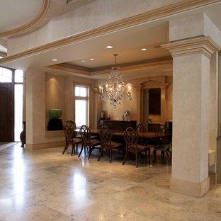 Ispirazione per un'ampia sala da pranzo aperta verso il soggiorno tradizionale con pareti multicolore, pavimento in pietra calcarea, camino sospeso e pavimento beige