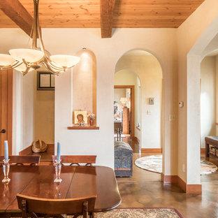 Aménagement d'une salle à manger ouverte sur la cuisine méditerranéenne de taille moyenne avec un mur orange, béton au sol, une cheminée standard, un manteau de cheminée en carrelage et un sol marron.