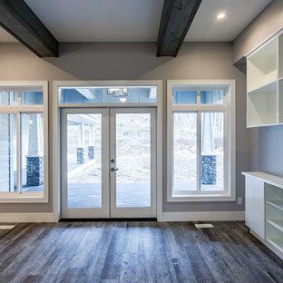 Esempio di una sala da pranzo aperta verso il soggiorno chic di medie dimensioni con pareti grigie, pavimento in laminato, nessun camino e pavimento marrone