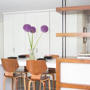 Ejemplo de comedor de cocina retro, grande, con paredes grises, suelo de madera oscura, chimenea tradicional y marco de chimenea de madera