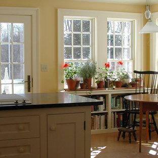 Immagine di una sala da pranzo aperta verso la cucina country di medie dimensioni con pareti gialle, pavimento in laminato, nessun camino e pavimento beige
