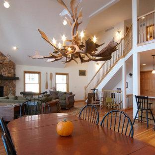 Diseño de comedor rural, de tamaño medio, abierto, con paredes blancas, suelo de madera clara, chimenea de esquina y marco de chimenea de piedra