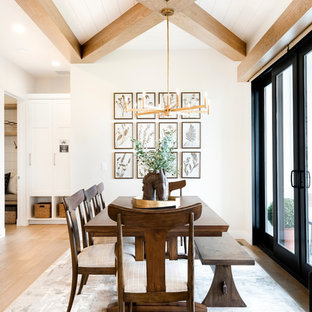 Dining room - farmhouse medium tone wood floor and brown floor dining room idea in Salt Lake City with white walls