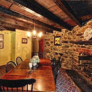 Ejemplo de comedor rústico, de tamaño medio, cerrado, con suelo de ladrillo, paredes amarillas, chimenea tradicional y marco de chimenea de piedra