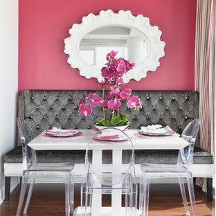 Réalisation d'une petit salle à manger tradition avec un mur rose et un sol en bois brun.