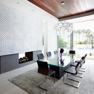 Modelo de comedor actual, grande, cerrado, con paredes blancas, chimenea de doble cara, marco de chimenea de hormigón y suelo de baldosas de cerámica