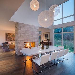 Идея дизайна: большая гостиная-столовая в современном стиле с белыми стенами, темным паркетным полом, двусторонним камином и фасадом камина из плитки