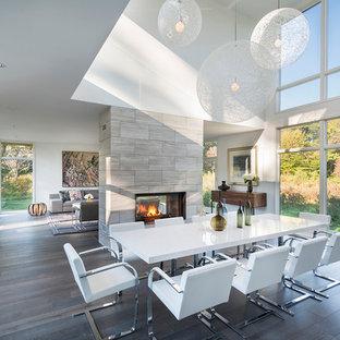 Esempio di una grande sala da pranzo aperta verso il soggiorno contemporanea con pareti bianche, parquet scuro, camino bifacciale e cornice del camino piastrellata
