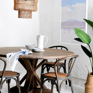 This is an example of a small beach style open plan dining room in Sydney with white walls, concrete flooring and white floors.