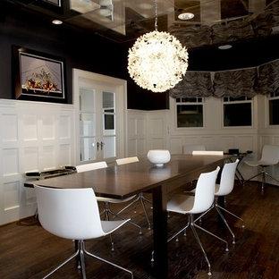 Immagine di una sala da pranzo minimal chiusa con pareti nere, parquet scuro e nessun camino