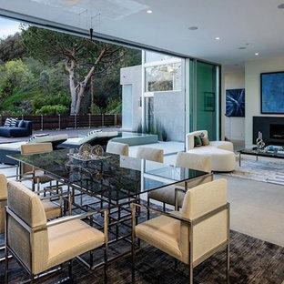 Новый формат декора квартиры: гостиная-столовая среднего размера в стиле модернизм с белыми стенами, бетонным полом, горизонтальным камином и фасадом камина из металла