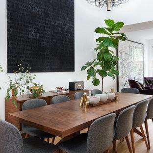 Esempio di una sala da pranzo aperta verso la cucina minimal di medie dimensioni con pareti bianche, parquet chiaro, nessun camino e pavimento marrone