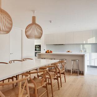 Modern inredning av ett stort kök med matplats, med vita väggar och ljust trägolv