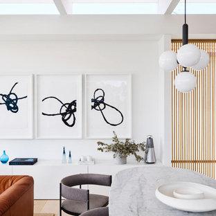 Cette photo montre une salle à manger ouverte sur le salon moderne avec un mur blanc, un sol en bois clair, un sol beige et un plafond en poutres apparentes.