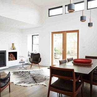 Неиссякаемый источник вдохновения для домашнего уюта: гостиная-столовая в стиле модернизм с белыми стенами, паркетным полом среднего тона, камином и фасадом камина из металла