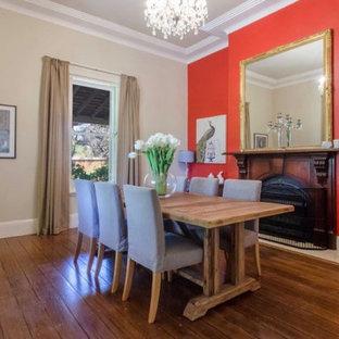 Foto di una grande sala da pranzo boho chic chiusa con pareti rosse, pavimento in legno massello medio, camino classico, cornice del camino in legno e pavimento marrone